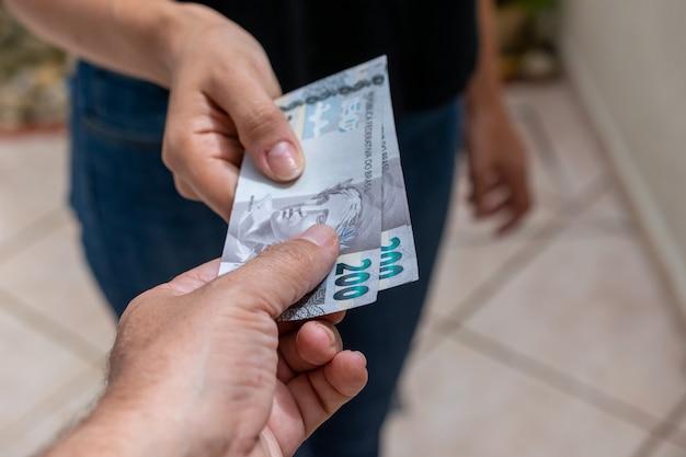 Consegna a mano nuove fatture di denaro brasiliano pagamento in contanti