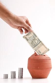 Deposito a mano cinquecento rupie indiane nota nel salvadanaio di argilla