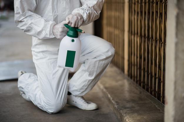 Specialista della disinfezione delle mani che indossa tuta per dispositivi di protezione individuale (dpi), guanti, maschera e occhiali trasparenti, pulizia con flacone di disinfettante spray pressurizzato per rimuovere covid-19