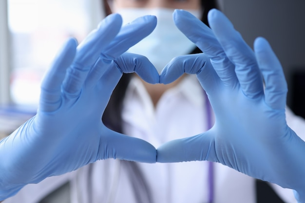 La mano del medico in guanti medicali protettivi sta coprendo il primo piano del cuore. concetto di cura cardiologica