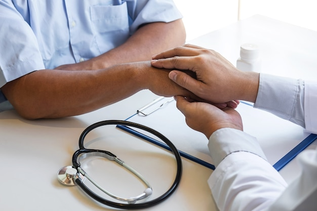 Mano del medico che tocca il paziente rassicurante per incoraggiamento ed empatia da sostenere durante la visita medica in ospedale.