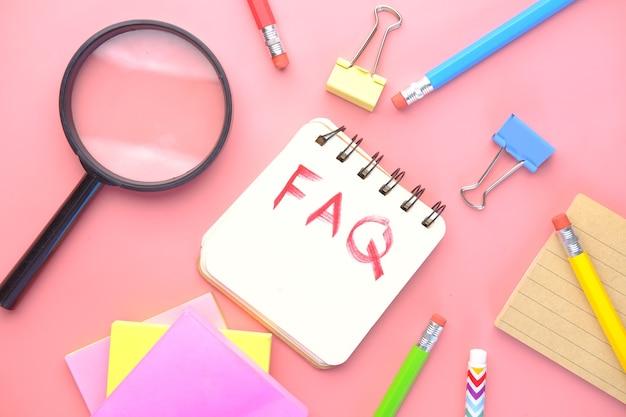 Testo di disegno a mano faq sul blocco note su sfondo rosa