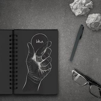 Lampadina disegnata a mano con la parola idea sul taccuino scuro come concetto