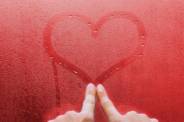 La mano disegna un cuore su una finestra di vetro con sfondo di gocce
