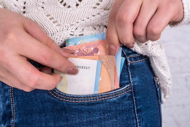 La mano estrae le banconote in euro dalla tasca dei jeans