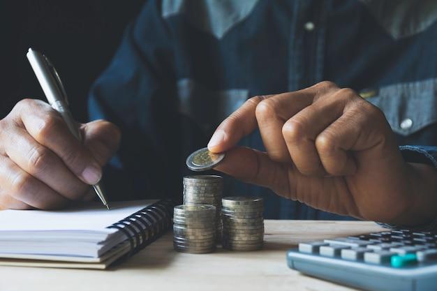 Goccia della mano una moneta con la pila della moneta dei soldi che cresce per l'affare.