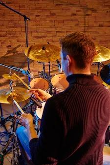 Mano del batterista con bacchette e tamburi