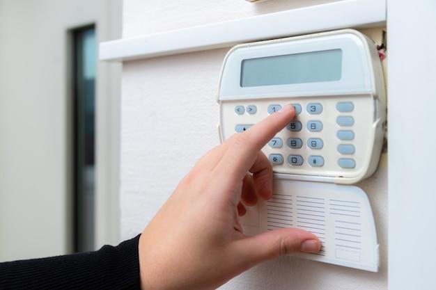 Mano che immette la password del sistema di allarme di un appartamento, casa o ufficio commerciale.