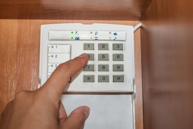 Mano inserendo la password del sistema di allarme di un appartamento, casa o ufficio. console di sorveglianza e antirapina e ladro