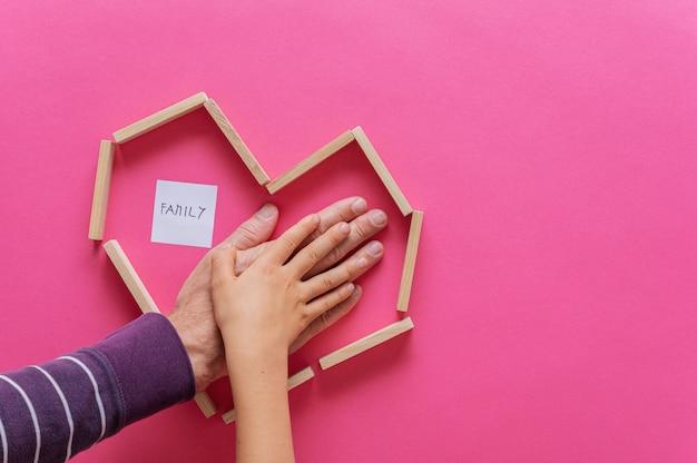 Mano di un padre e di un bambino impilati uno sopra l'altro all'interno di una forma di cuore fatta di pioli di legno.