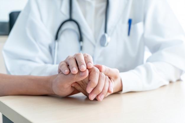 Mano del medico femminile che tiene sul suo paziente anziano