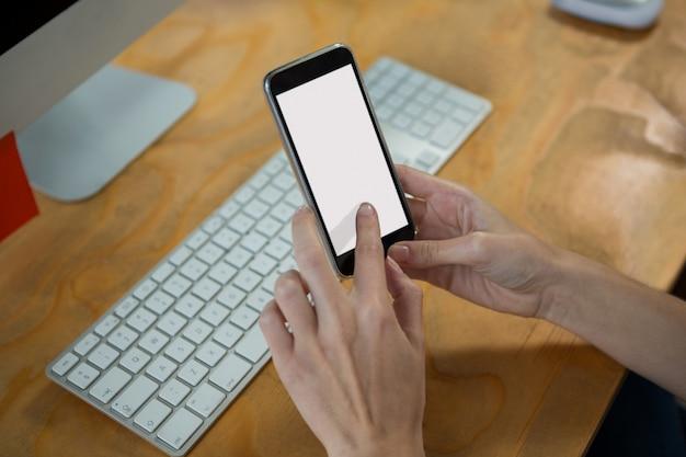 Mano del designer grafico femminile utilizzando il telefono cellulare