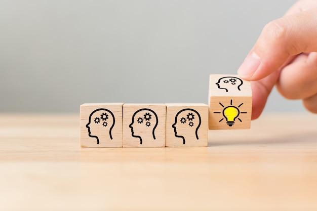 Capovolgi il cubo di legno con il simbolo umano testa e l'icona della lampadina. concept idea creativa e innovazione
