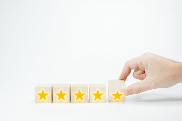 Mano capovolgere il cubo di legno a forma di cinque stelle miglior servizio eccellente valutazione per la soddisfazione a cinque stelle per aumentare la valutazione dell'azienda