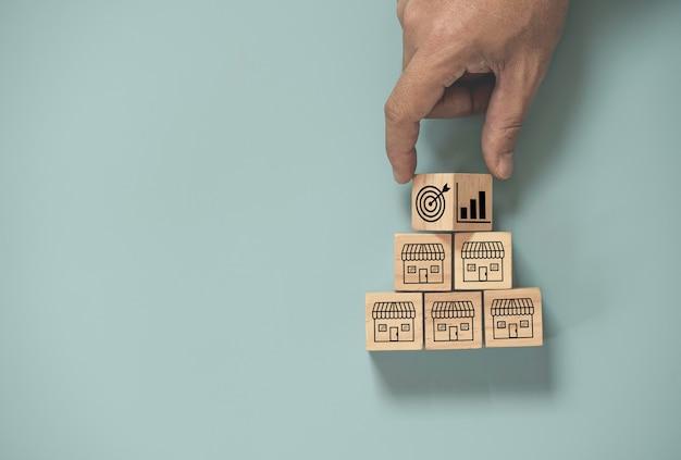 Scorrimento della mano tra il target e la crescita delle vendite nel negozio per lo shopping che stampa lo schermo sul cubo di legno su sfondo blu, espande il concetto di franchising e centro commerciale.