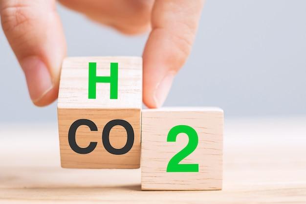 Lanciare a mano blocchi di cubo di legno con co2 (anidride carbonica), passare al testo h2 (idrogeno) sullo sfondo della tabella. free carbon, energie alternative e concetti di cambiamento climatico globale