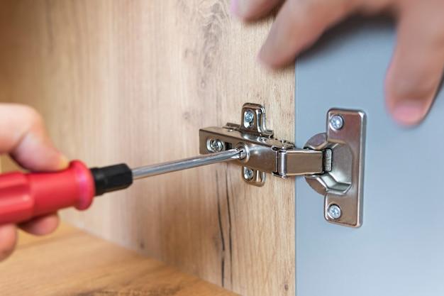 Una mano di un assemblatore di mobili che regola un meccanismo per aprire la porta del tavolo dell'ufficio con un cacciavite. avvicinamento. concetto di riparazione domestica. autoassemblaggio di mobili.