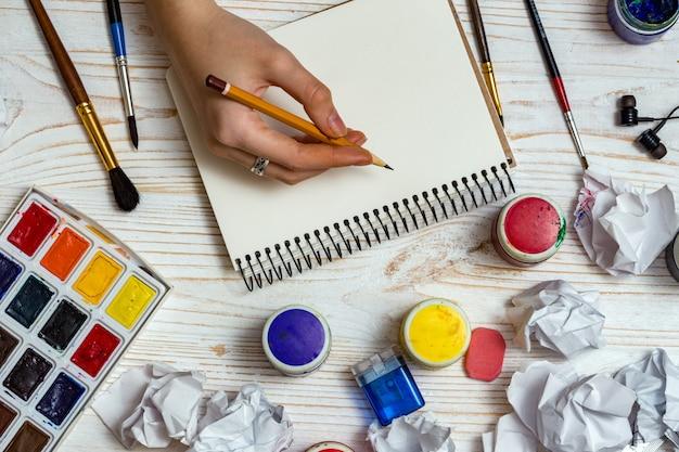 La mano dell'artista della ragazza e le pagine dell'album, le vernici, le matite, l'olio, il pennello su uno sfondo di legno