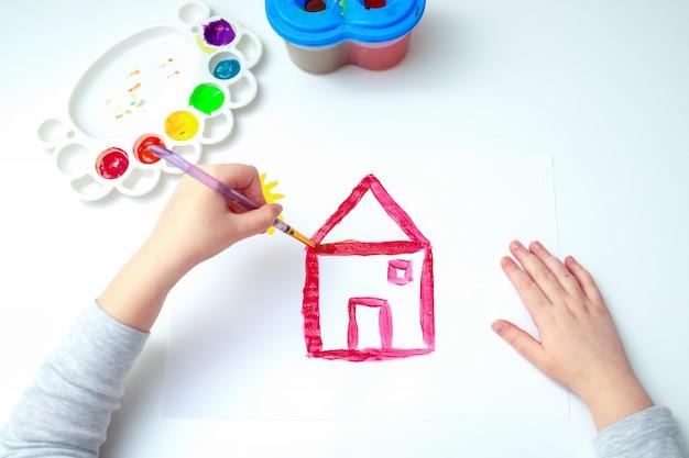 Mano di una ragazza che disegna una casa rossa.