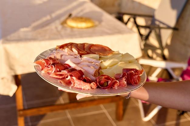 Mano di una ragazza che tiene un piatto di carne fredda e formaggio diversi, non vengono mostrate facce