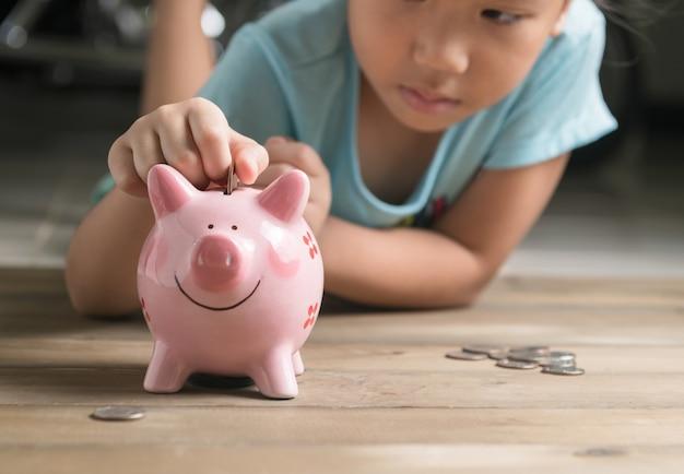 Mano ragazza mise moneta per salvadanaio, risparmiando denaro per l'istruzione