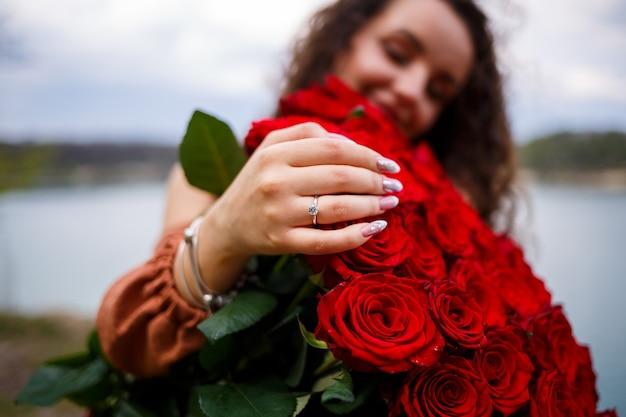 Mano di una ragazza con un primo piano della fede nuziale su un mazzo di rose rosse
