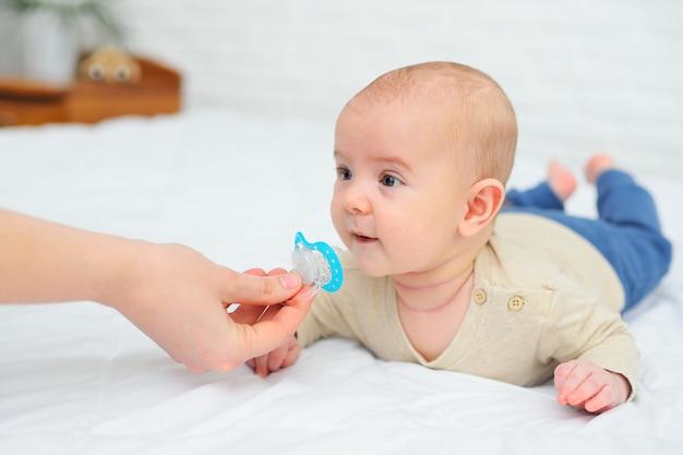 La mano dà un ciuccio a suo figlio bambino su bianco