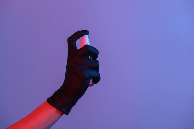 La mano nel guanto tiene lo spray antisettico. luce al neon rosso-blu