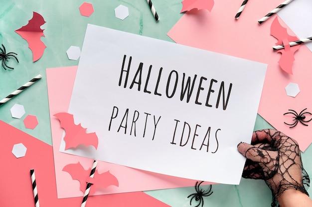 Mano in guanto tiene la pagina con testo idee per feste di halloween.