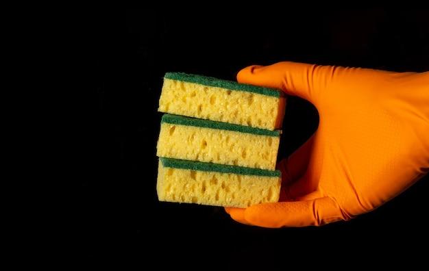 La mano in un guanto tiene tre salviette su sfondo nero