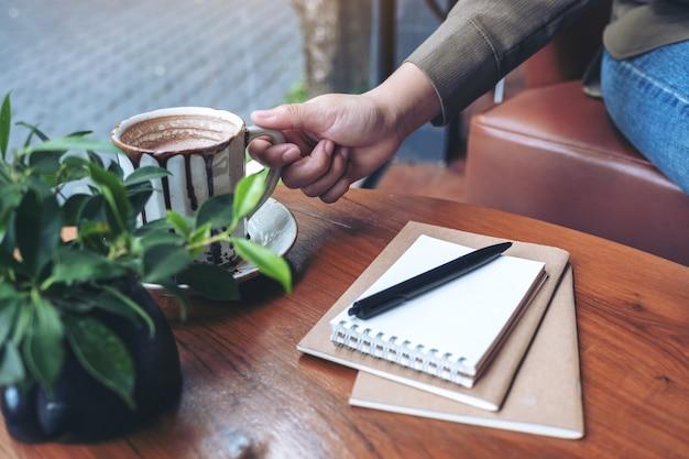 Mano che afferra una tazza di caffè caldo con i notebook sul tavolo di legno