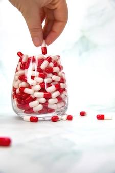 Una mano che afferra la mano piena di medicinali, capsule di vitamine, farmaci, farmaci. salute, spazio della copia del fondo di concetto di affari
