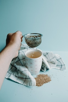 Una mano che afferra un distillatore di tè davanti a una tazza di tè su uno sfondo blu pastello