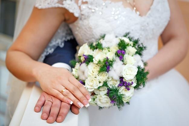 Mano dello sposo e della sposa a una festa di nozze