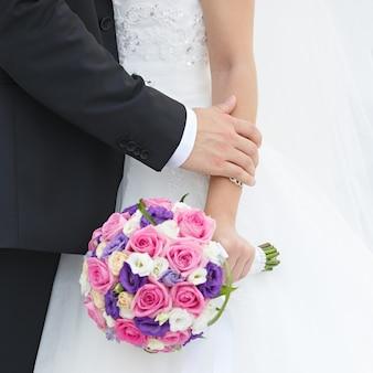 Mano dello sposo e della sposa con fedi nuziali a una festa di nozze