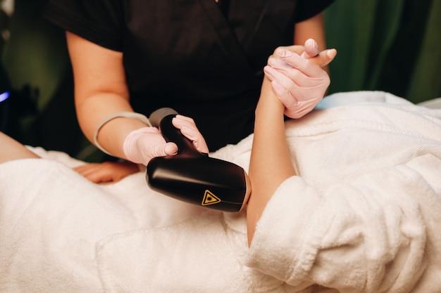 Procedura di rimozione dei peli delle mani eseguita in salone a una giovane donna utilizzando un apparecchio speciale
