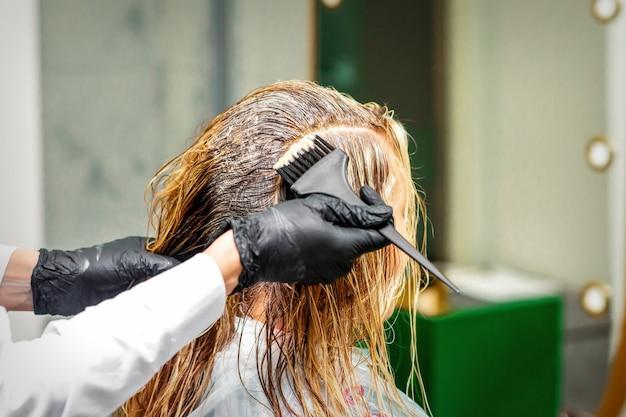 Mano di un parrucchiere in guanti neri che applicano tintura ai capelli femminili in un salone di bellezza beauty