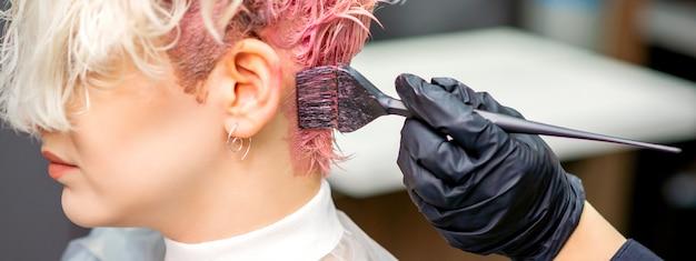 Mano del parrucchiere che tinge i capelli della giovane donna caucasica in colore rosa