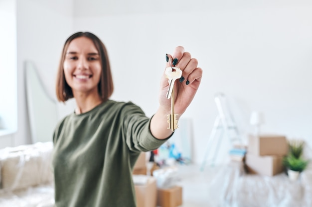 Mano di felice giovane donna in abbigliamento casual che tiene la chiave dal nuovo appartamento o casa