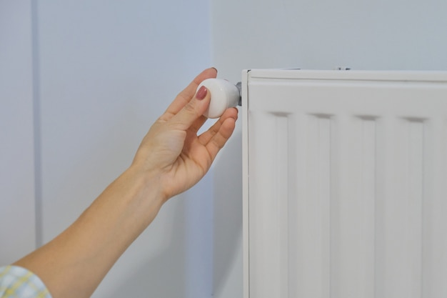 La mano sul radiatore di riscaldamento regola la temperatura con il regolatore del termostato