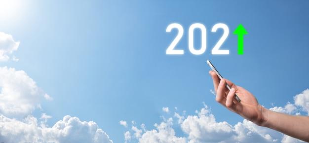Tenere in mano 2021 icona positiva sullo sfondo del cielo. pianificare la crescita positiva del business nel concetto dell'anno 2021. piano dell'uomo d'affari e aumento degli indicatori positivi nella sua attività, concetti di business in crescita.