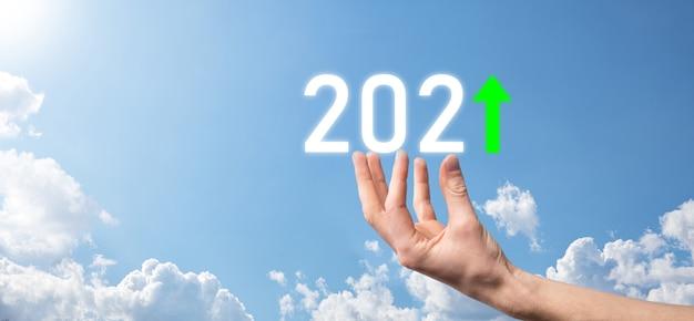 Tenere in mano 2021 icona positiva sullo sfondo del cielo. pianificare la crescita positiva del business nel concetto dell'anno 2021. piano dell'uomo d'affari e aumento degli indicatori positivi nella sua attività, concetti di business in crescita. Foto Premium