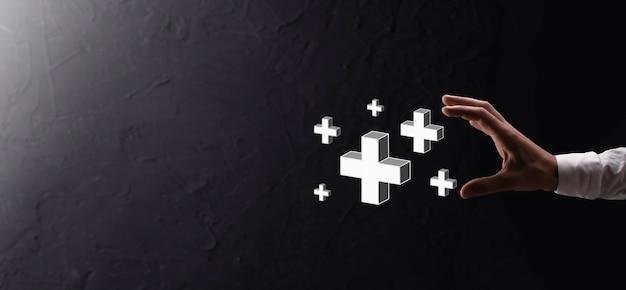 Tenere in mano l'icona 3d più, l'uomo tiene in mano offre cose positive come profitto, benefici, sviluppo, csr rappresentato dal segno più. la mano mostra il segno più