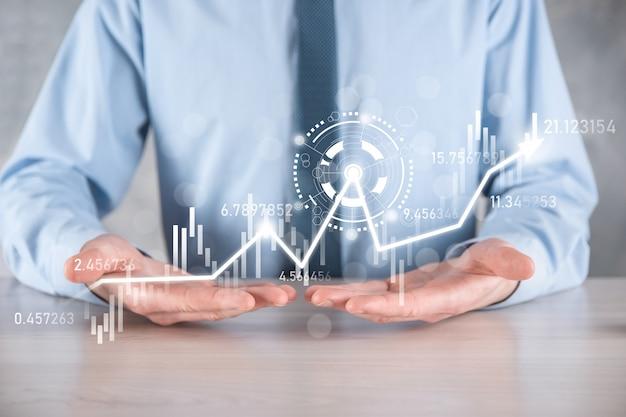 In mano tieni il grafico finanziario delle attività bancarie e investi in un punto di investimento del mercato azionario,economico