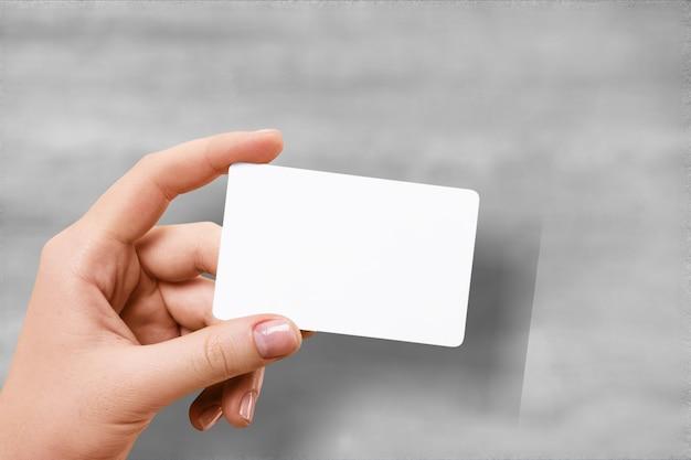 Tenere in mano un modello di carta traslucida in bianco con angoli arrotondati.