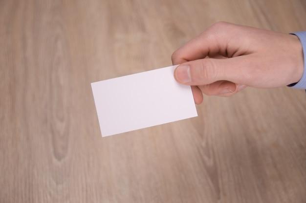 Mockup di carta bianca vuota della stretta della mano con angoli arrotondati. semplice biglietto da visita mock up modello tenendo il braccio. porta biglietti da visita in plastica sul lato anteriore. controlla il design della carta offset. marchio aziendale.