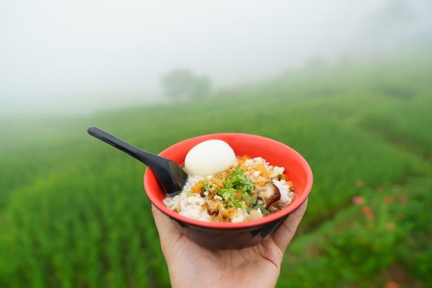 Tenere in mano il riso bollito con carne di maiale e uova