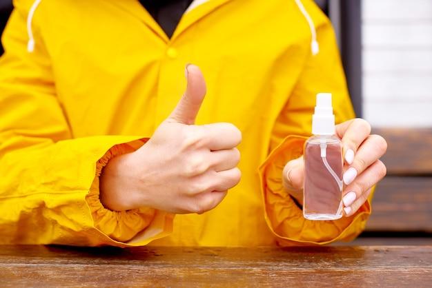 Tenere in mano una bottiglia di soluzione alcolica disinfettante spray disinfettante
