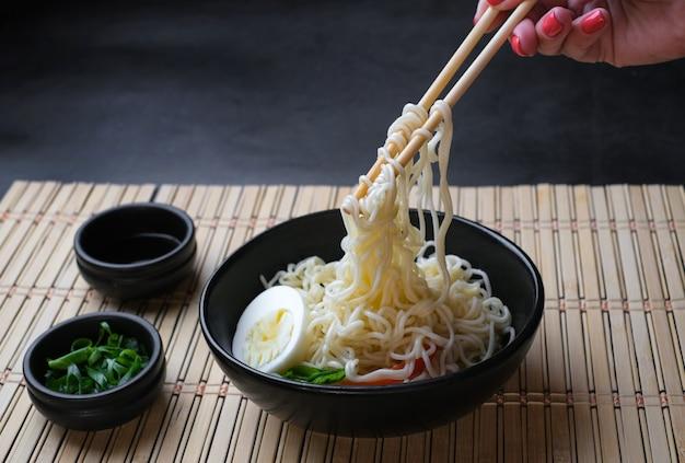 Tenere in mano le bacchette tagliatelle con vapore su sfondo nero asian noodle junk food concept