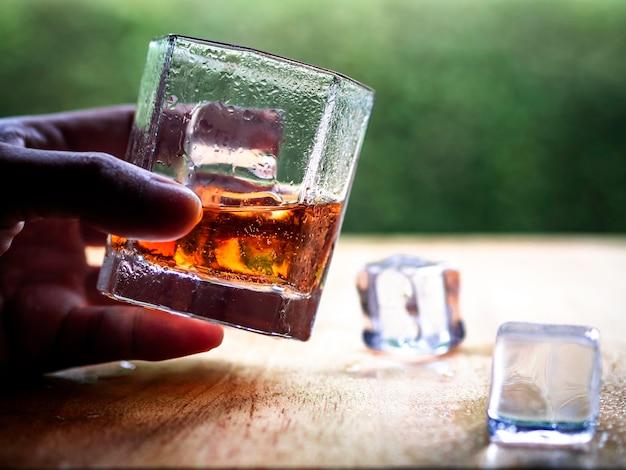 Tenere in mano il bicchiere di whisky fresco con lo sfondo della natura